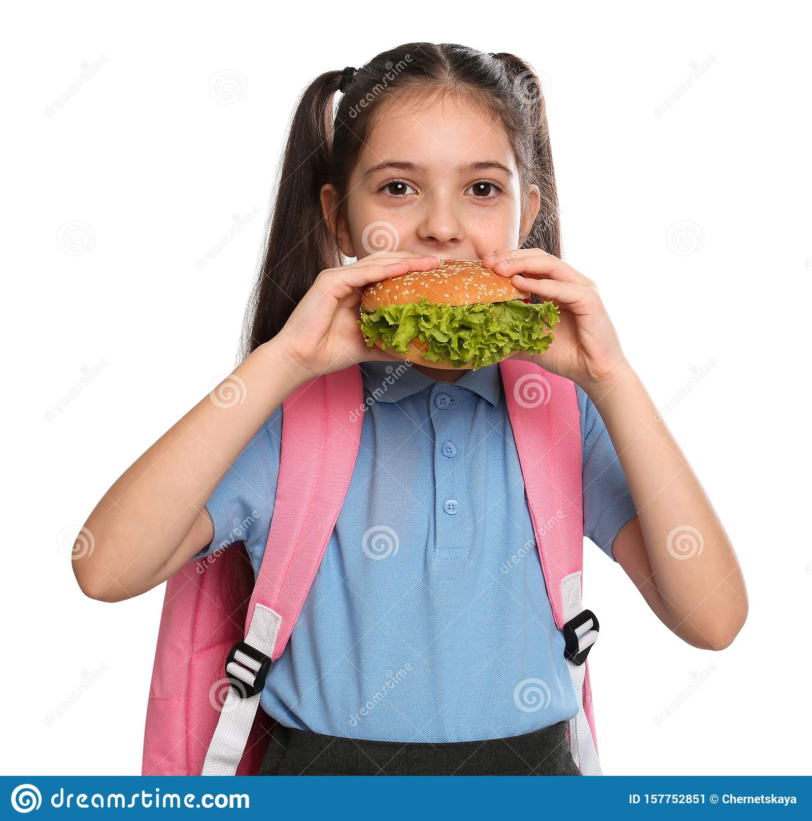 Little girl eating burger on white background. food for school lunch