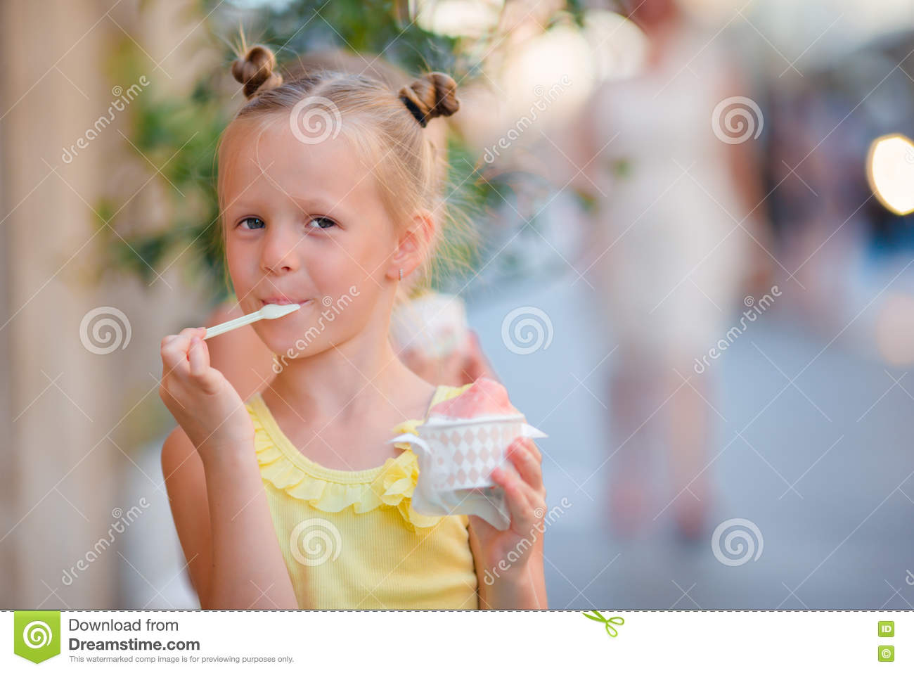 little girl eating ice-cream outdoors at summer. cute kid enjoying