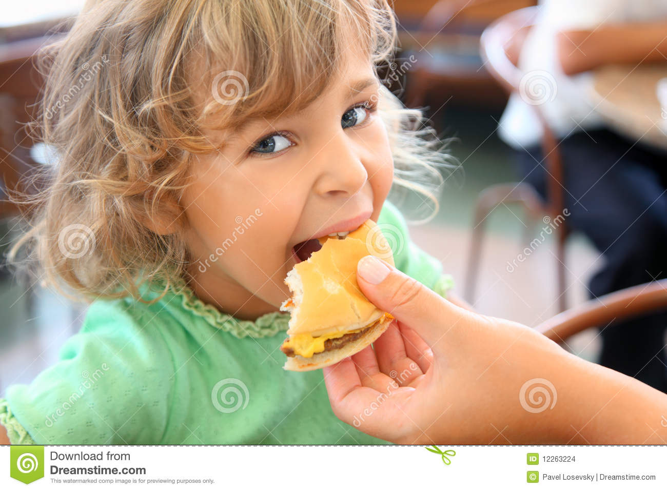 Little girl eats hamburger from mothers s hand