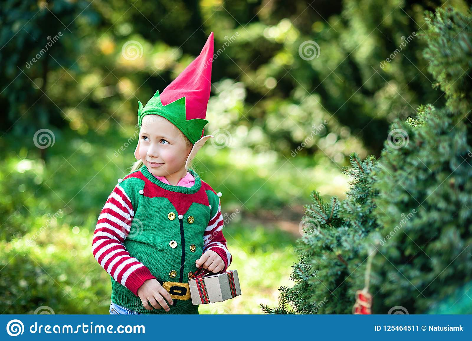 Little girl in elf sweater and hat waiting for a Christmas in the wood. Half-length portrait of a little child near the christmas