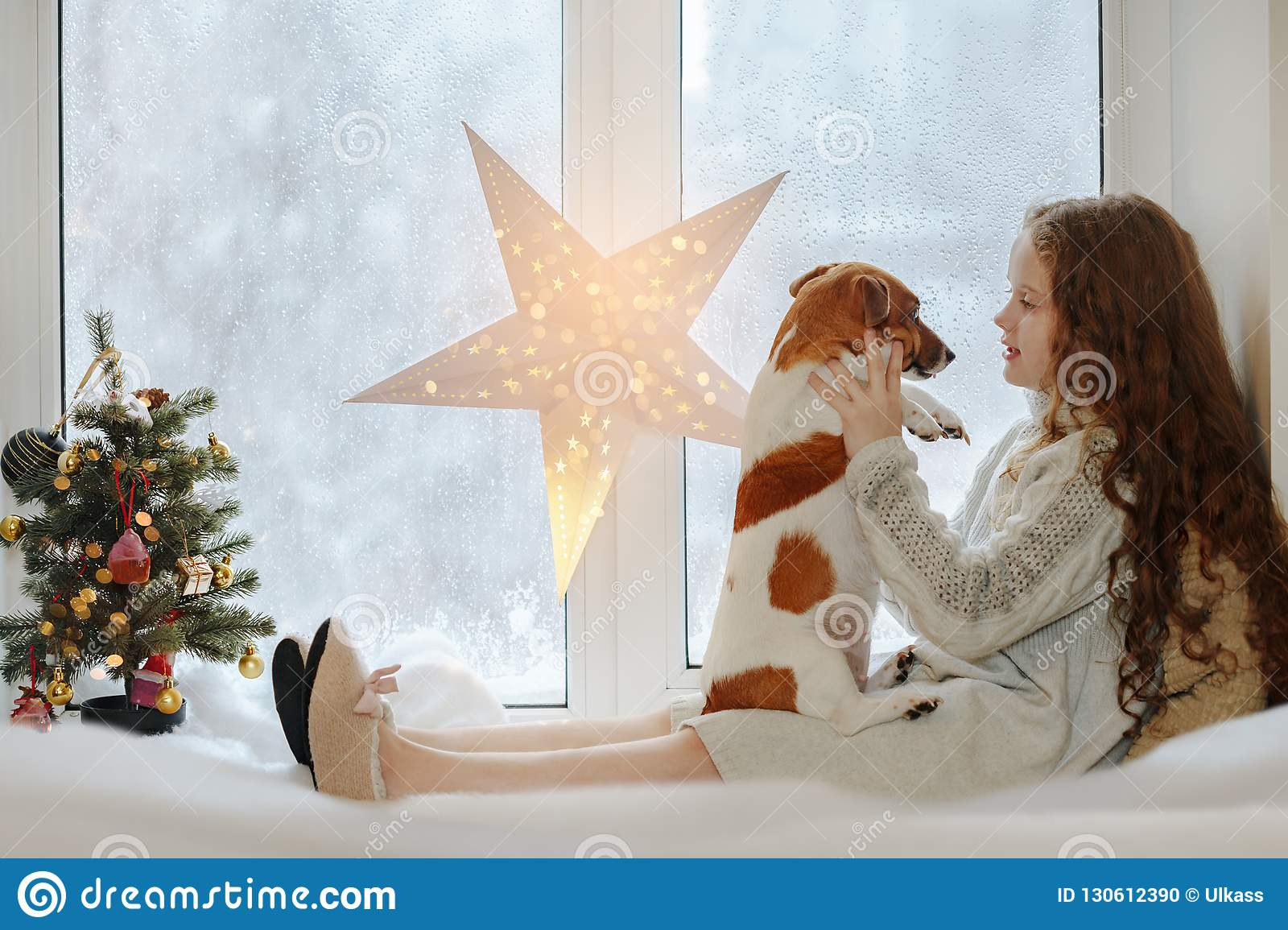 Little girl embracing her puppy dog, sitting on window and waiti