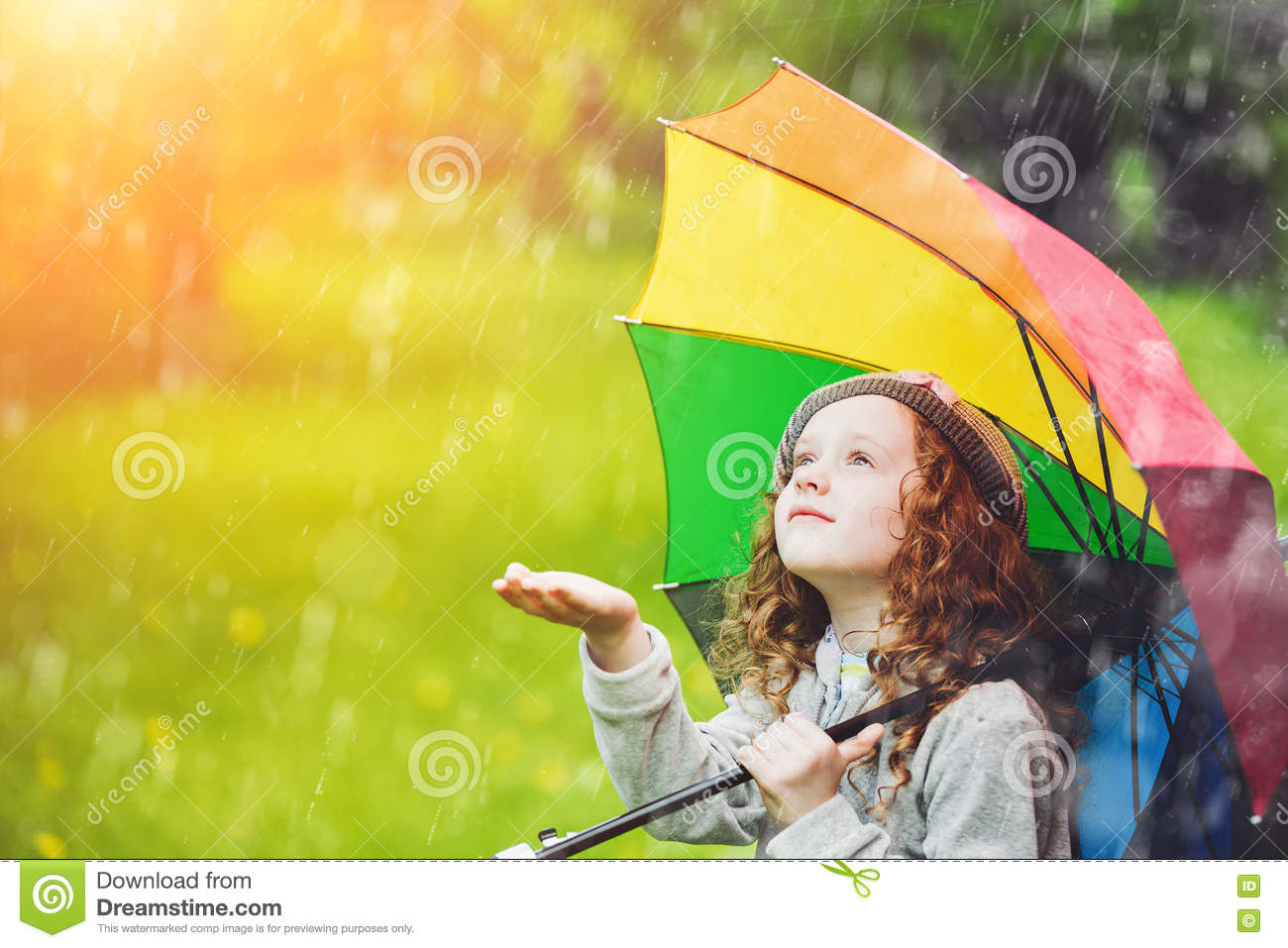 Little girl enjoy to spring rain.