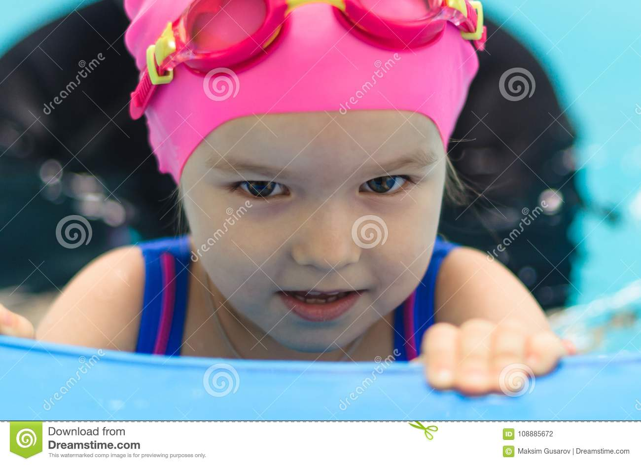 A little girl of European appearance in the pool smiling and looking at camera