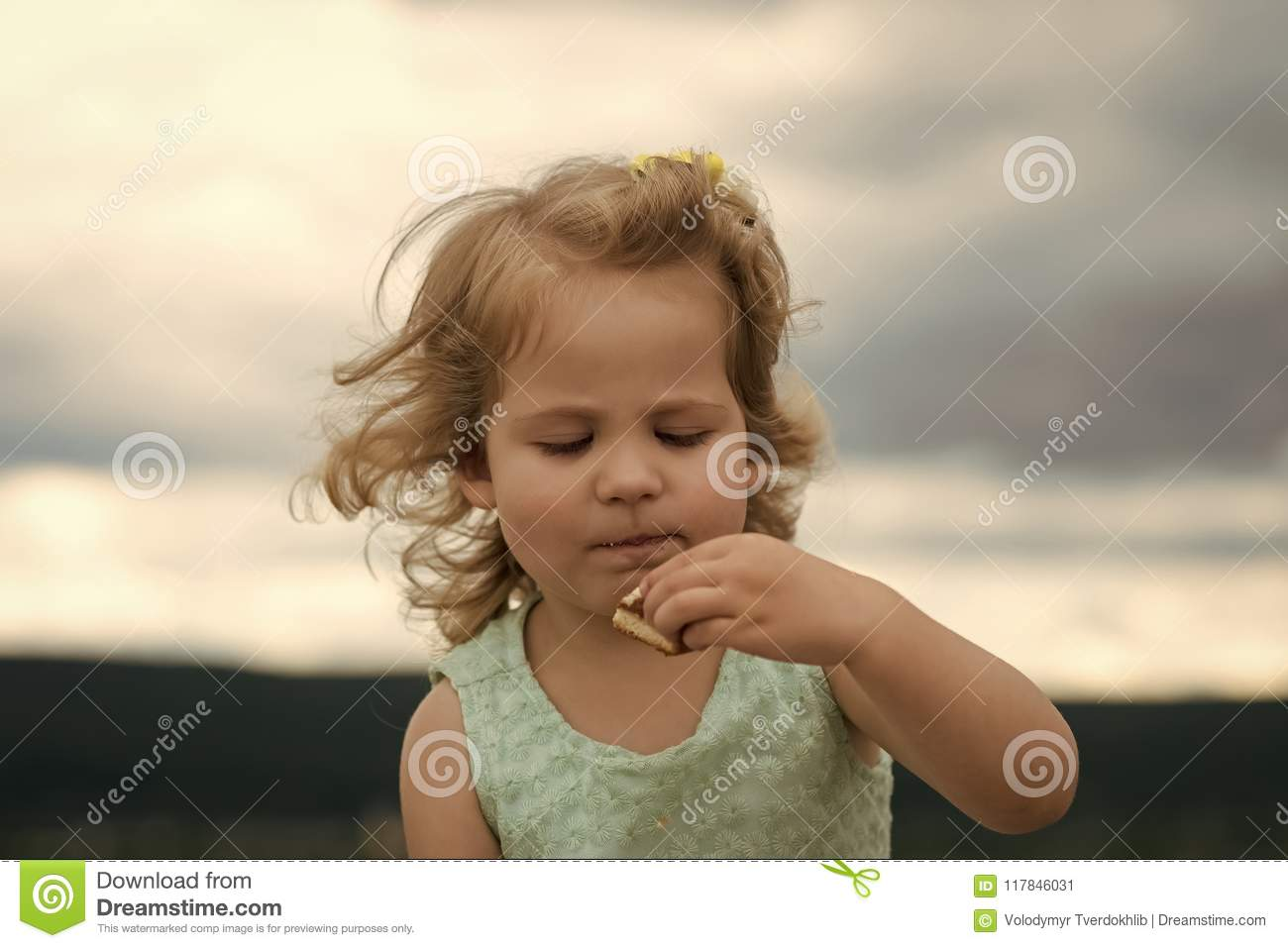c5b3dc7c627a Little girl face portrait in your advertisnent. Girl child eat cookie on summer  day on cloudy sky. Food