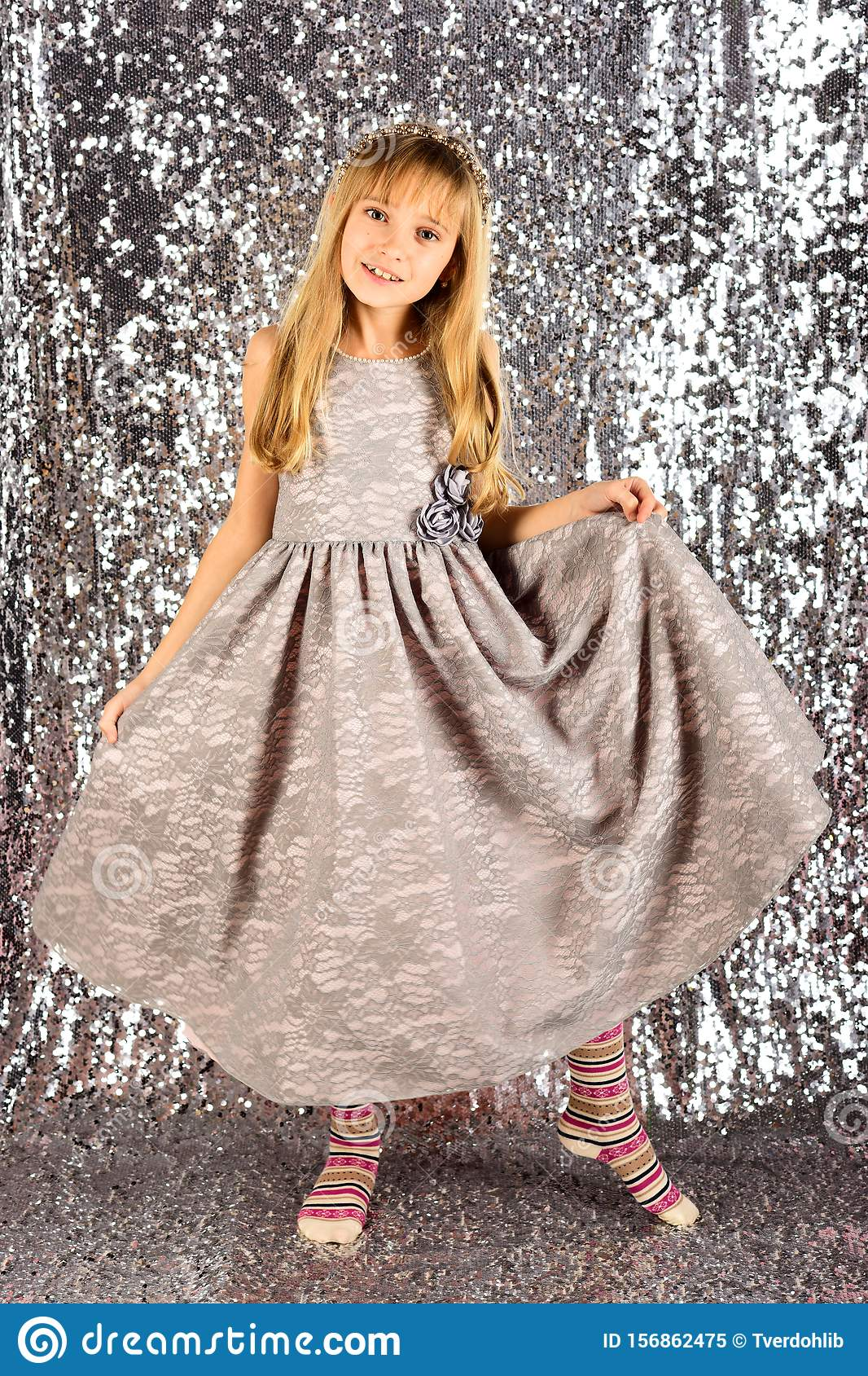 Little girl in fashionable dress, prom. Fashion model on silver background, beauty. Look, hairdresser, makeup. Child
