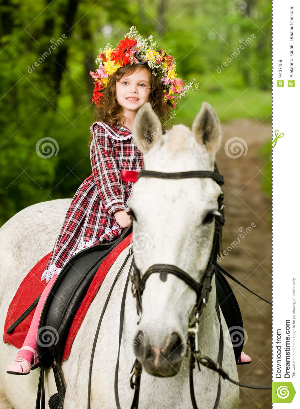 Little girl in floral wreath riding horse
