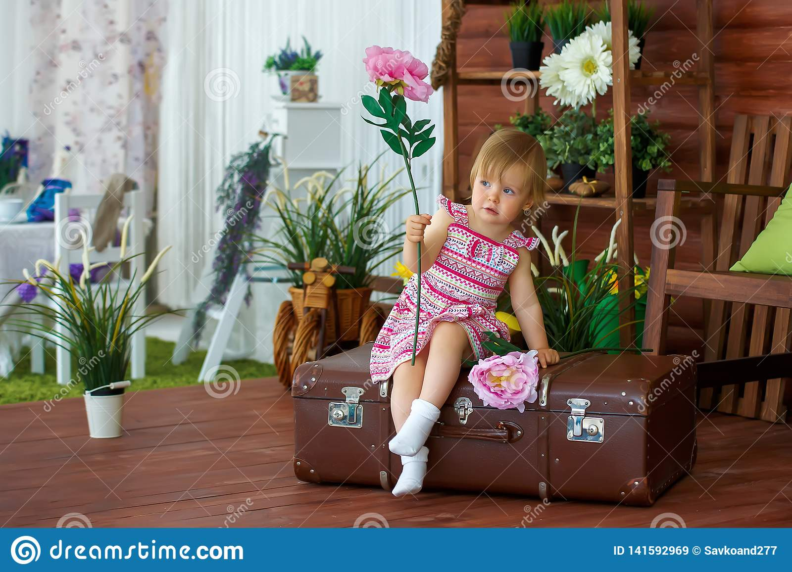 Little girl with a flower on a suitcase