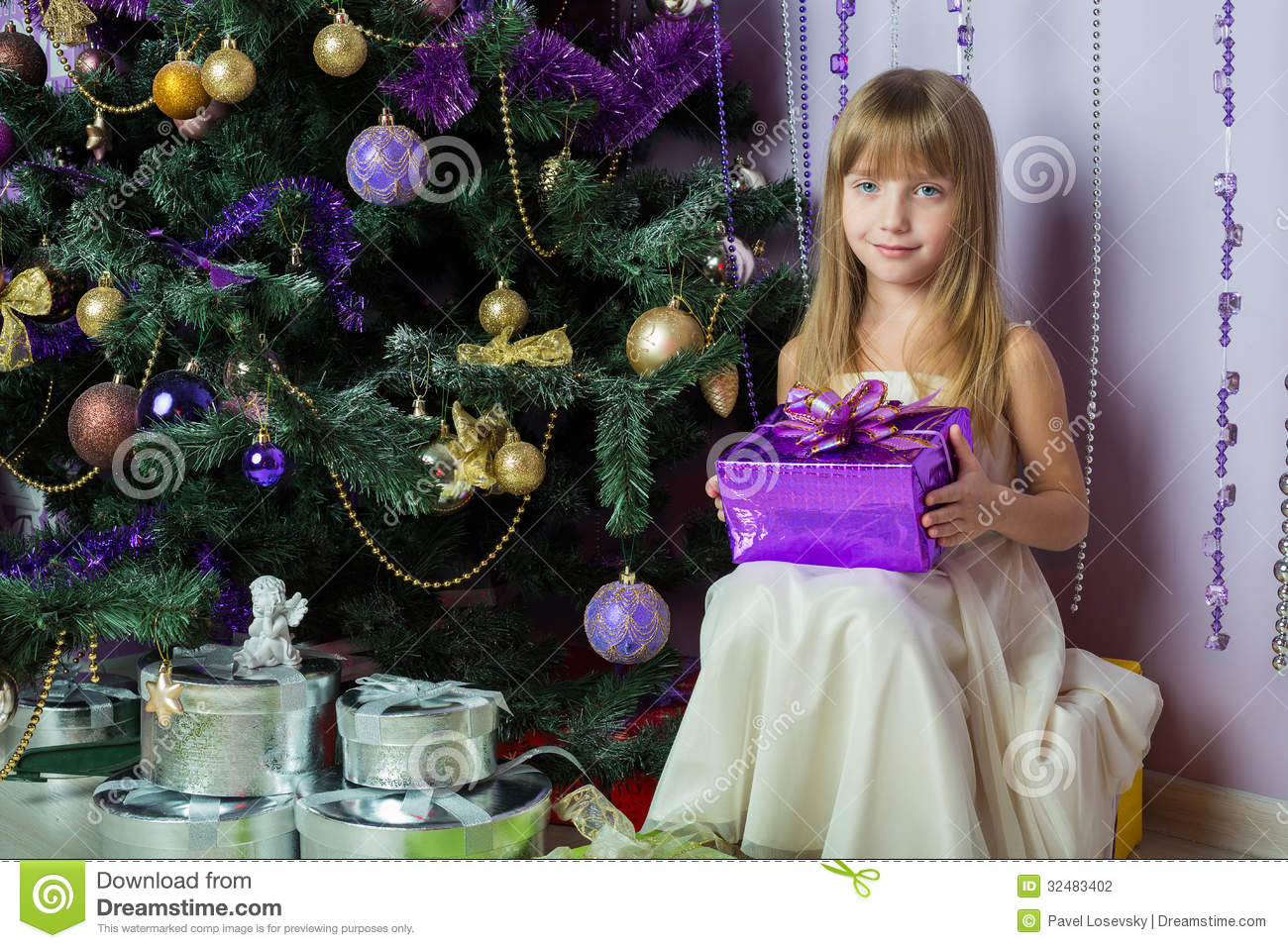 Little Girl With A Gift Sitting Under The Christmas Tree