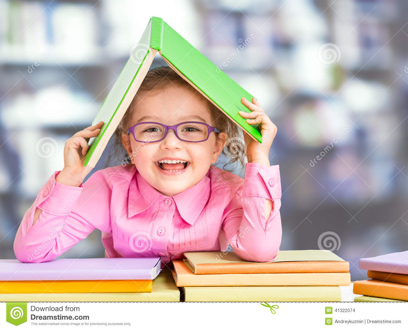 Little girl in glasses under book roof or house