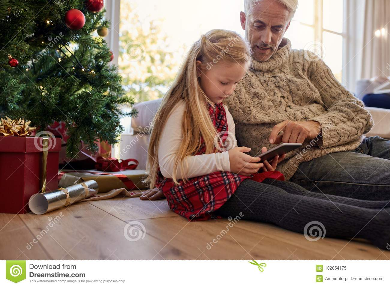 Little girl with grandfather sitting by christmas tree and using