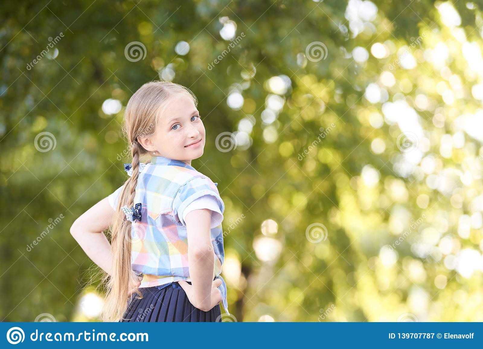Little girl in green sunny forest along. Fun schoolgirl outside. Selective focus