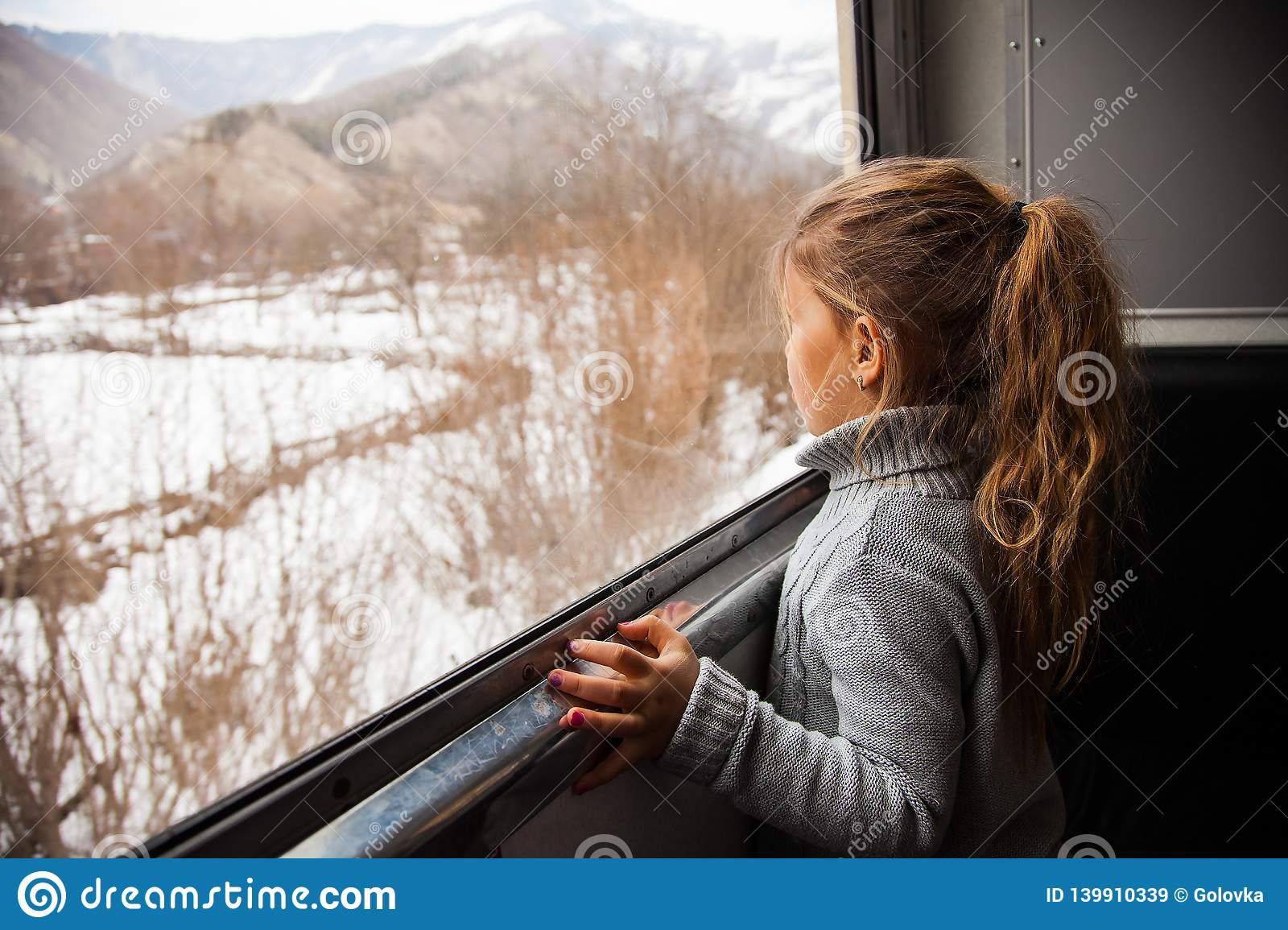 Little girl in grey sweater travelling by Kukushka train in Georgia and looking throught the window