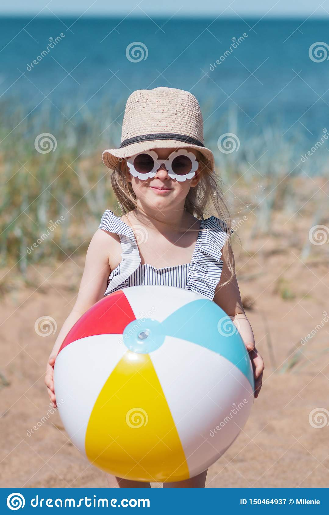 Little girl in hat playing on beach with ball, sunny summer day