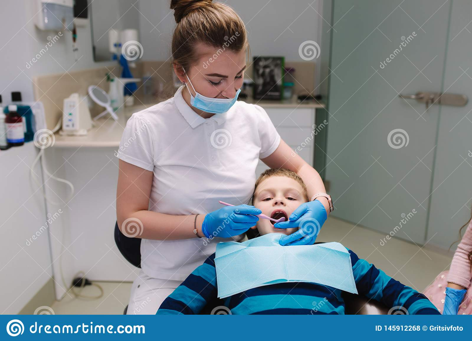 Little girl help female dentist, new teeth examinationand treatment of cavities