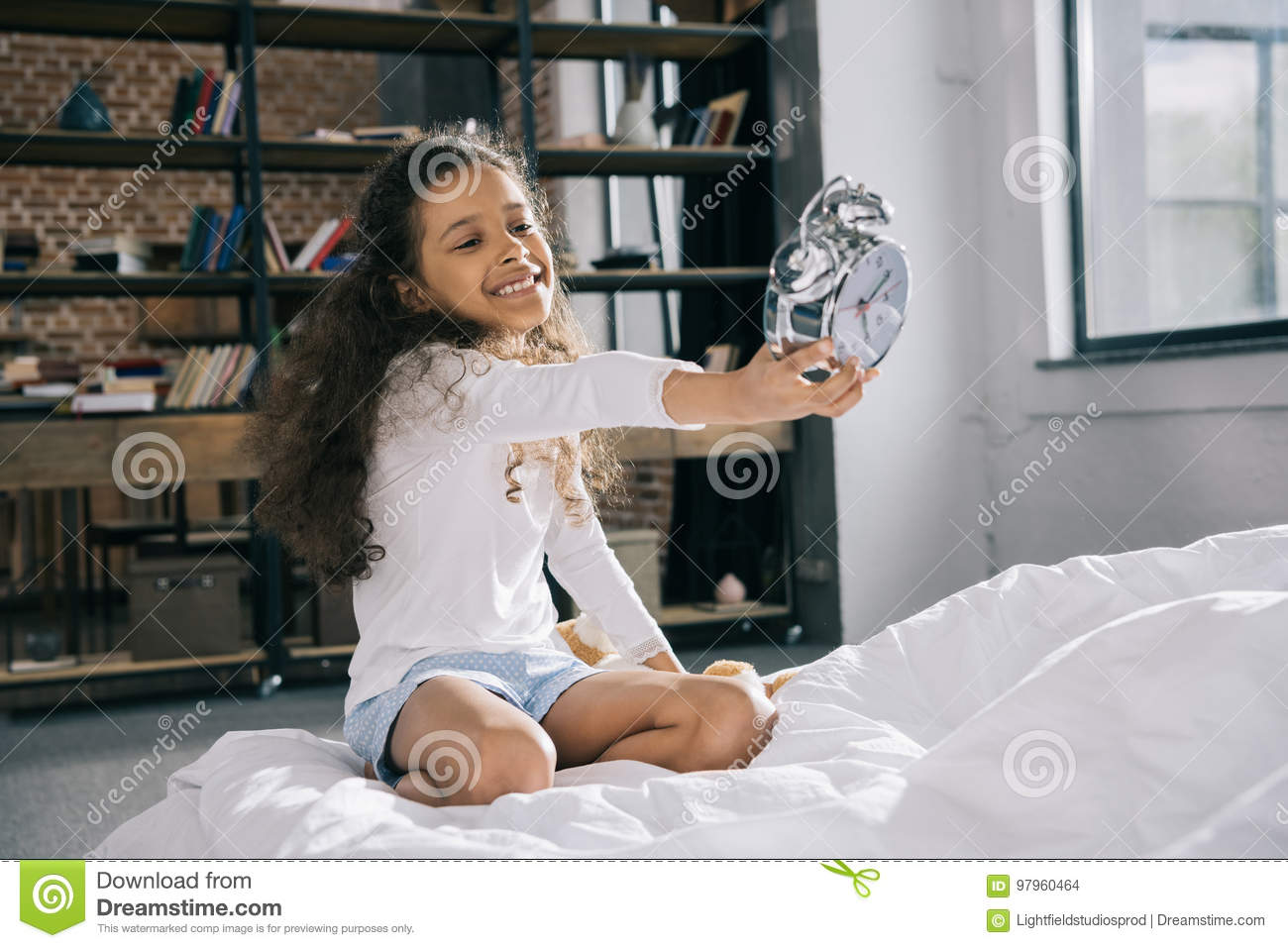 Little girl holding alarm clock while sitting on bed