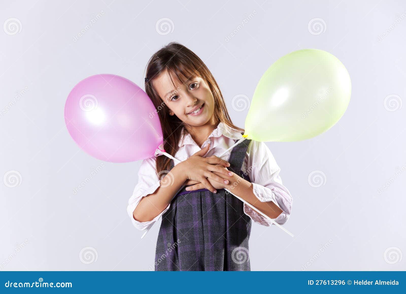 Little girl holding color ballons