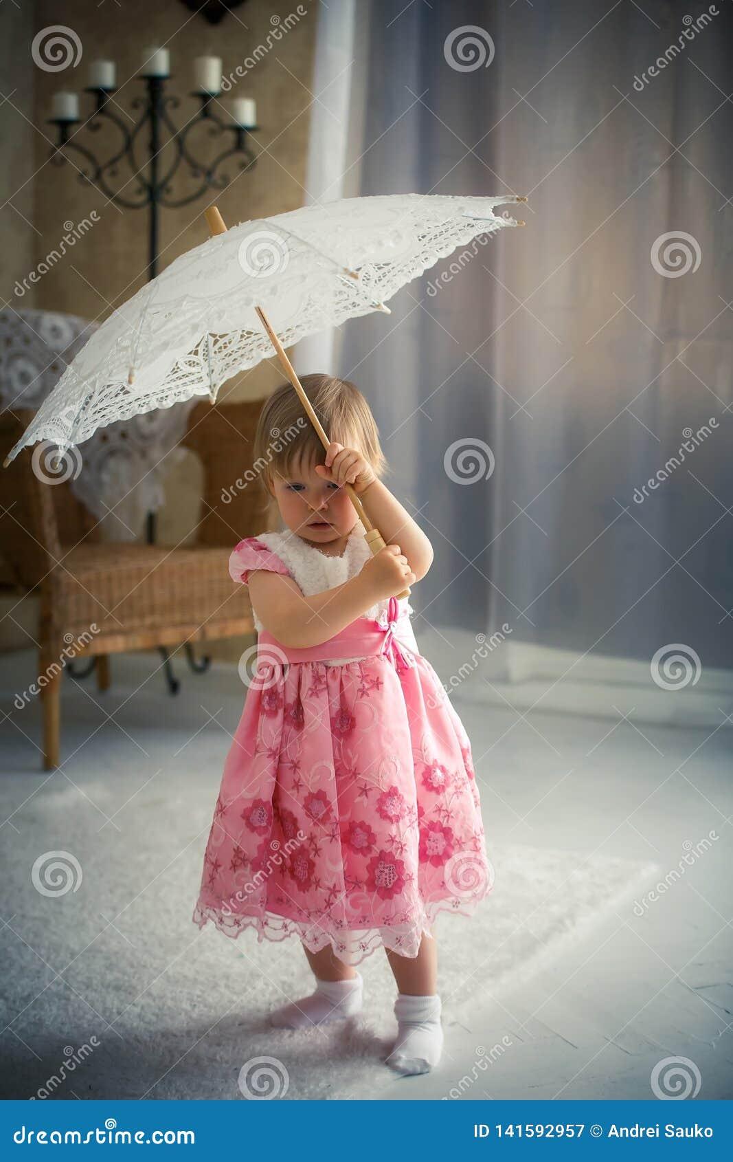 Little girl holding an umbrella for the sun