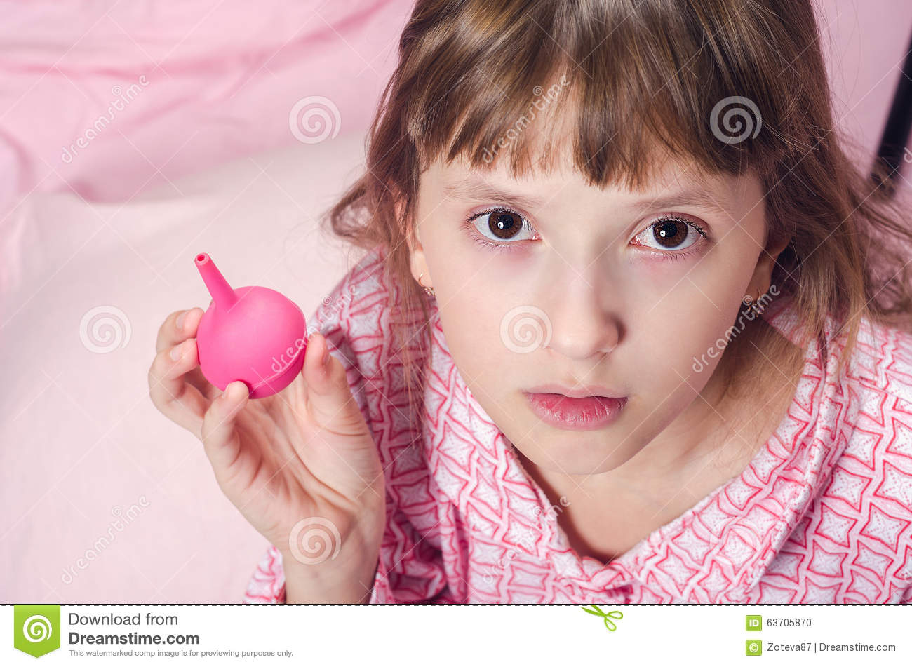 the little girl holds an enema in hand stock photo image
