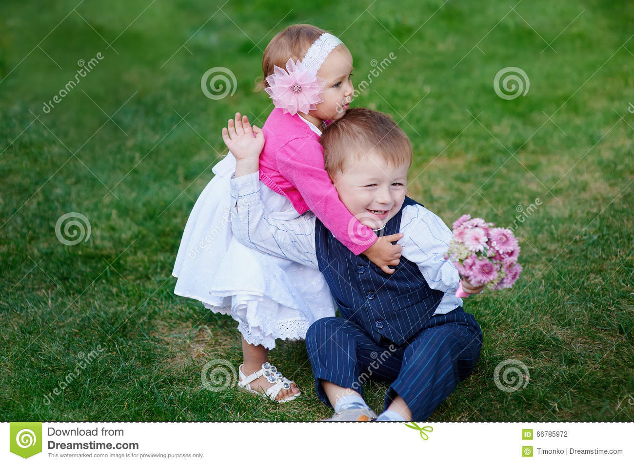 5b975f9ea630 Little Girl Hugging A Boy With A Bouquet Of Flowers In Park Stock ...