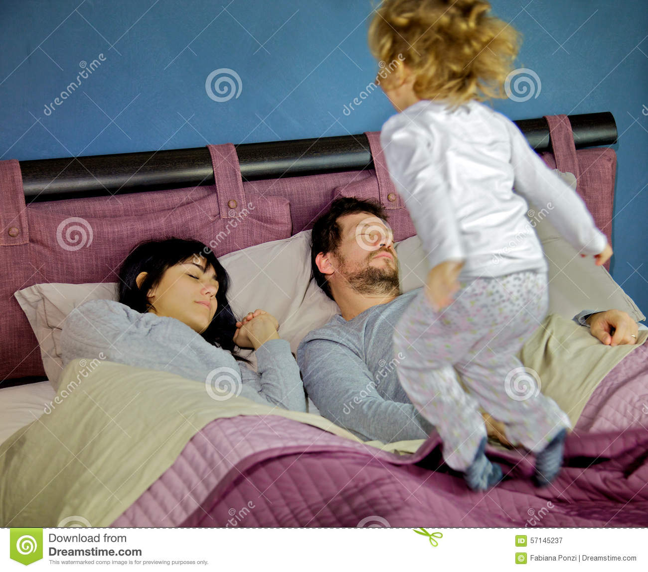 Little girl jumping on bed while parents are sleeping