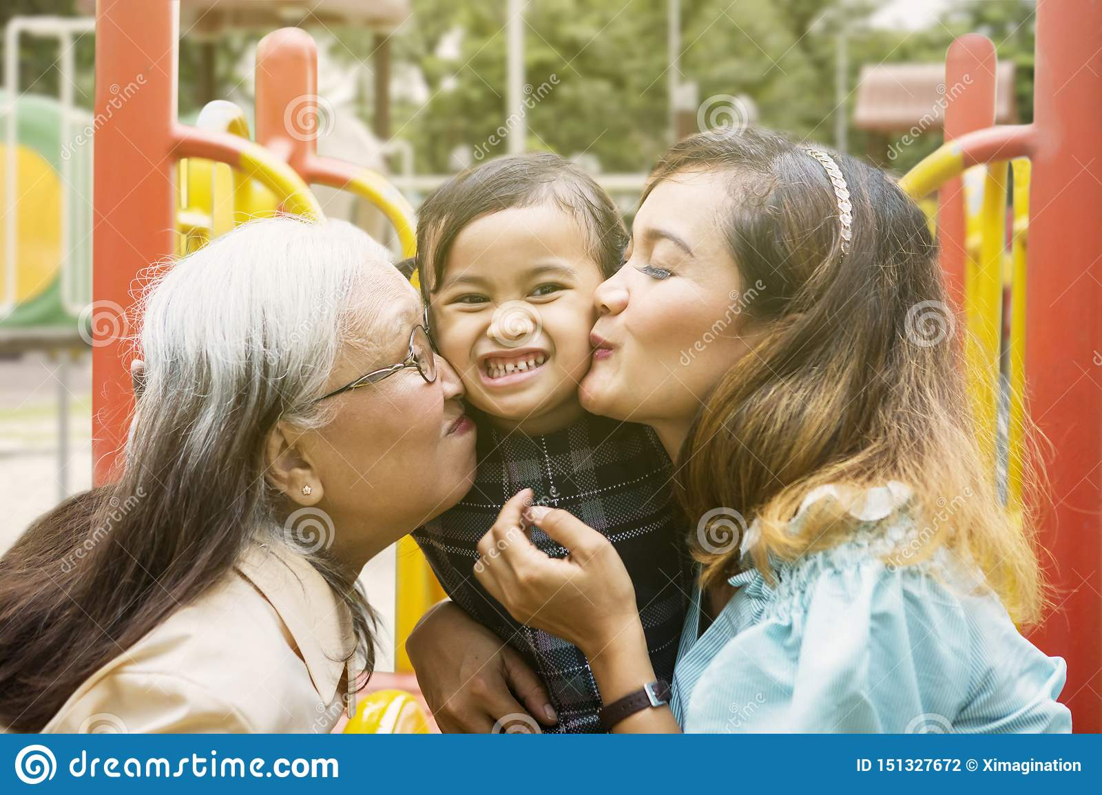 Little girl kissed by her mother and grandmother