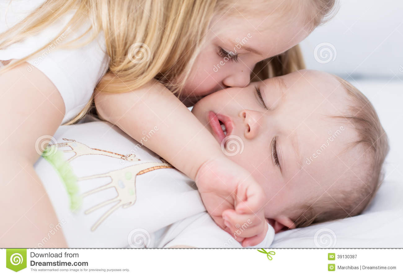little girl kisses a sleeping baby brother stock photo