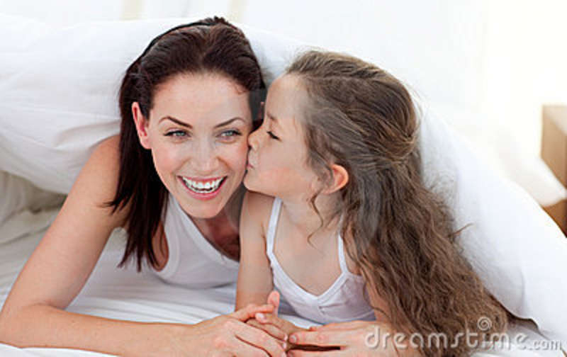 Very young girl kissing mom