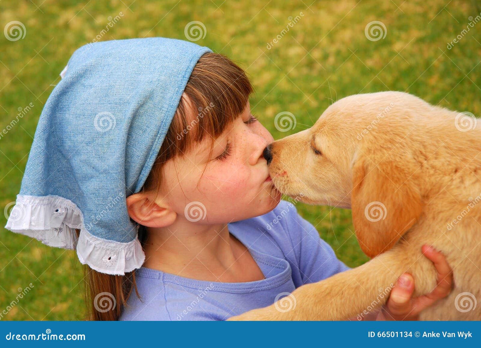 Little girl kissing puppy