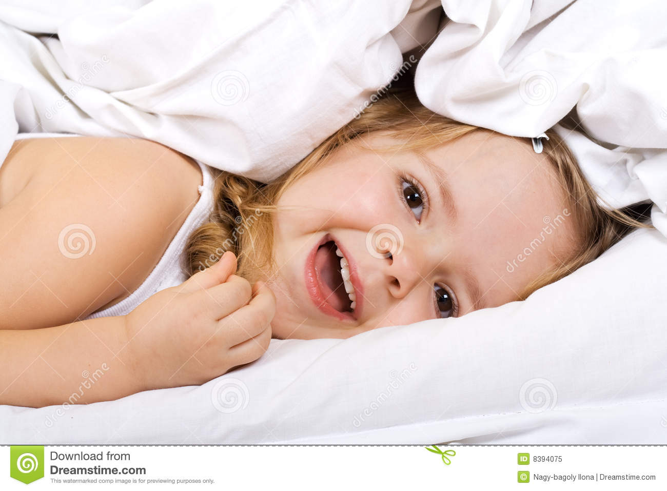 little girl laying in bed under the quilt royalty free