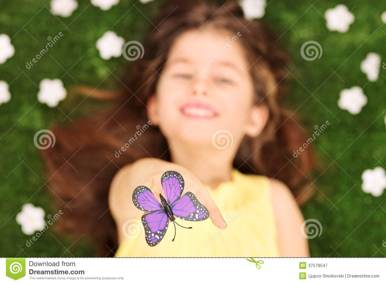 Little girl laying in meadow and reaching to touch butterfly