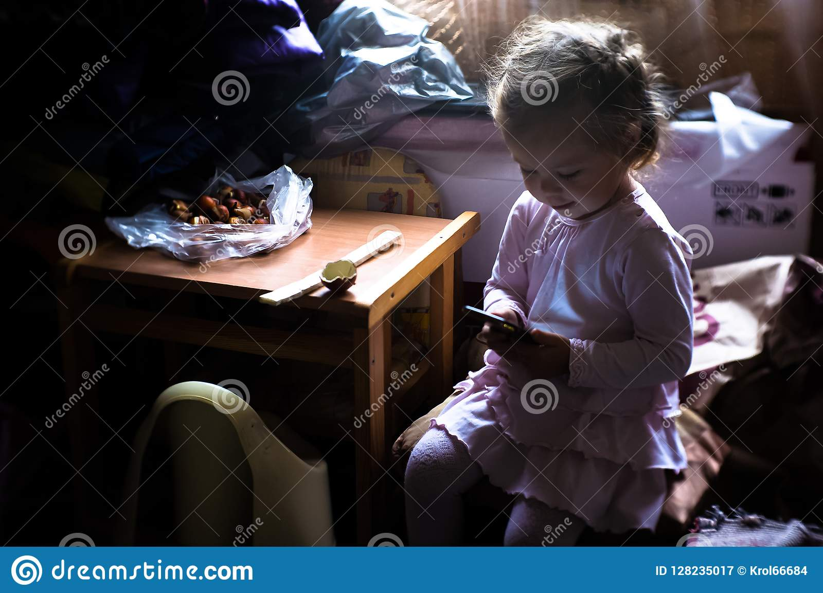 A little girl learns about the Internet through a mobile phone.