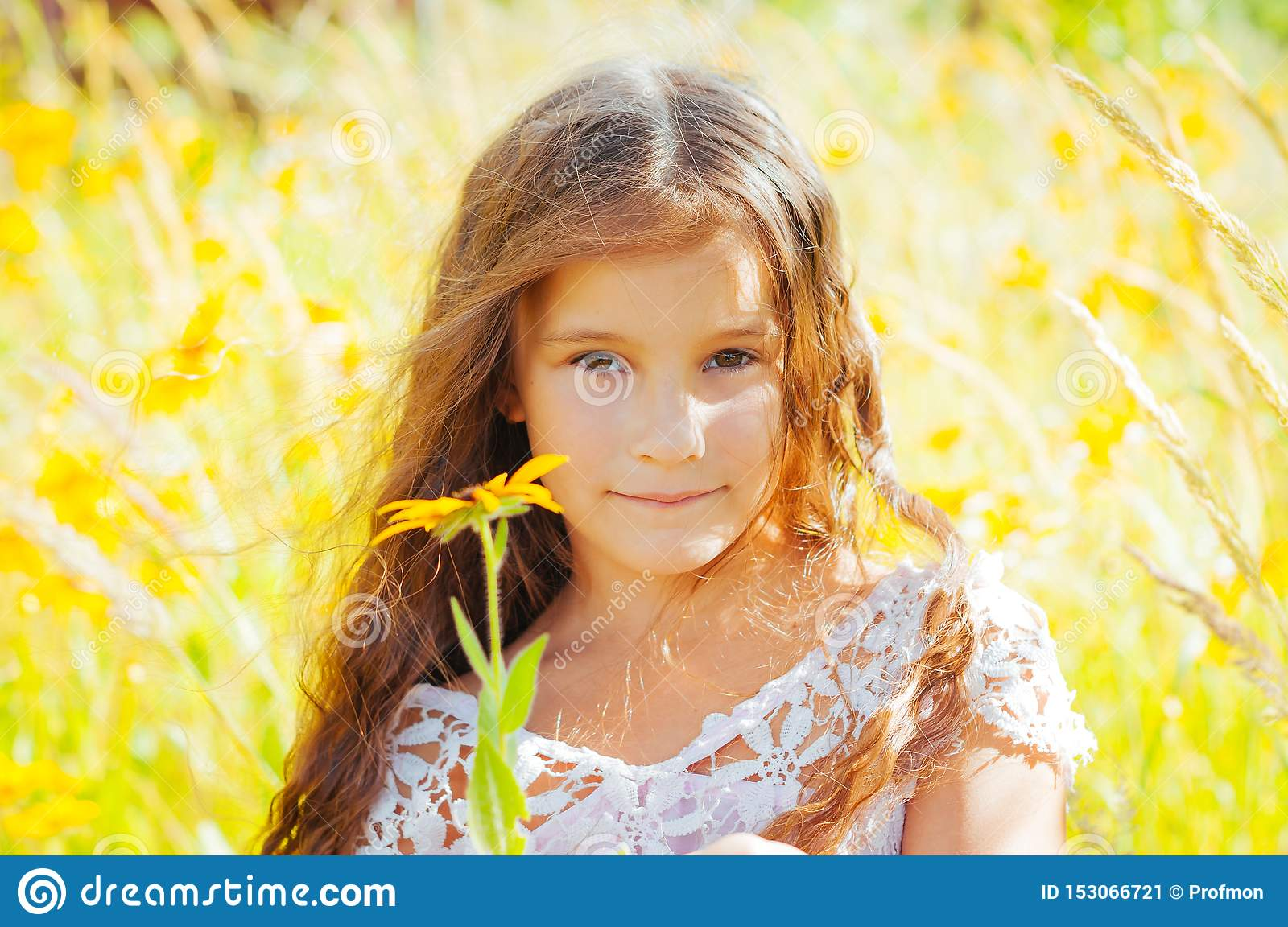 Little girl with long hair in a white dress rejoices in a field with flowers