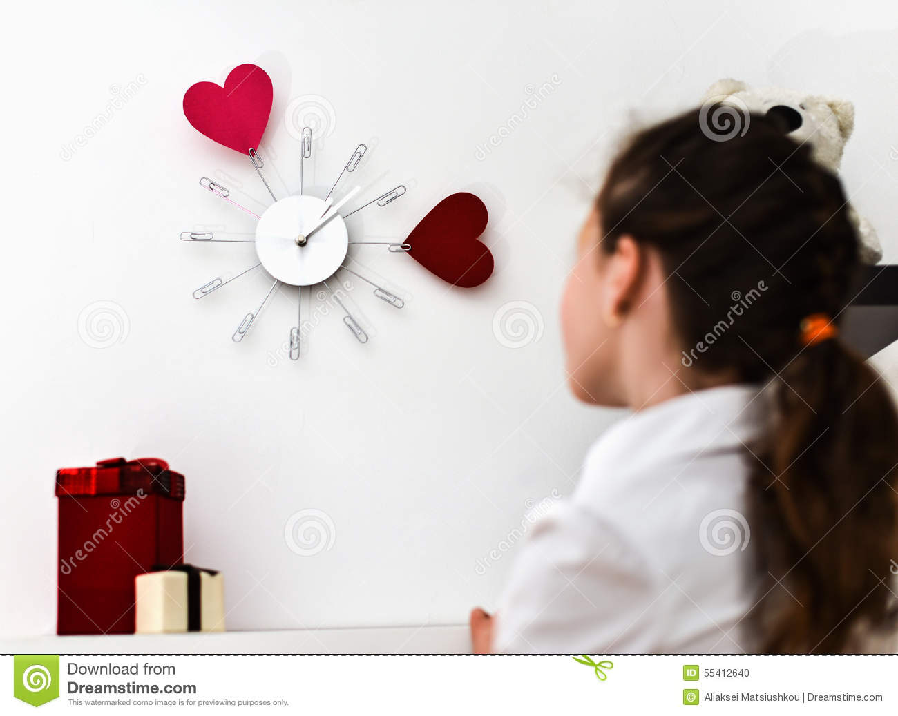 little girl looking at a clock on the wall stock photo image of