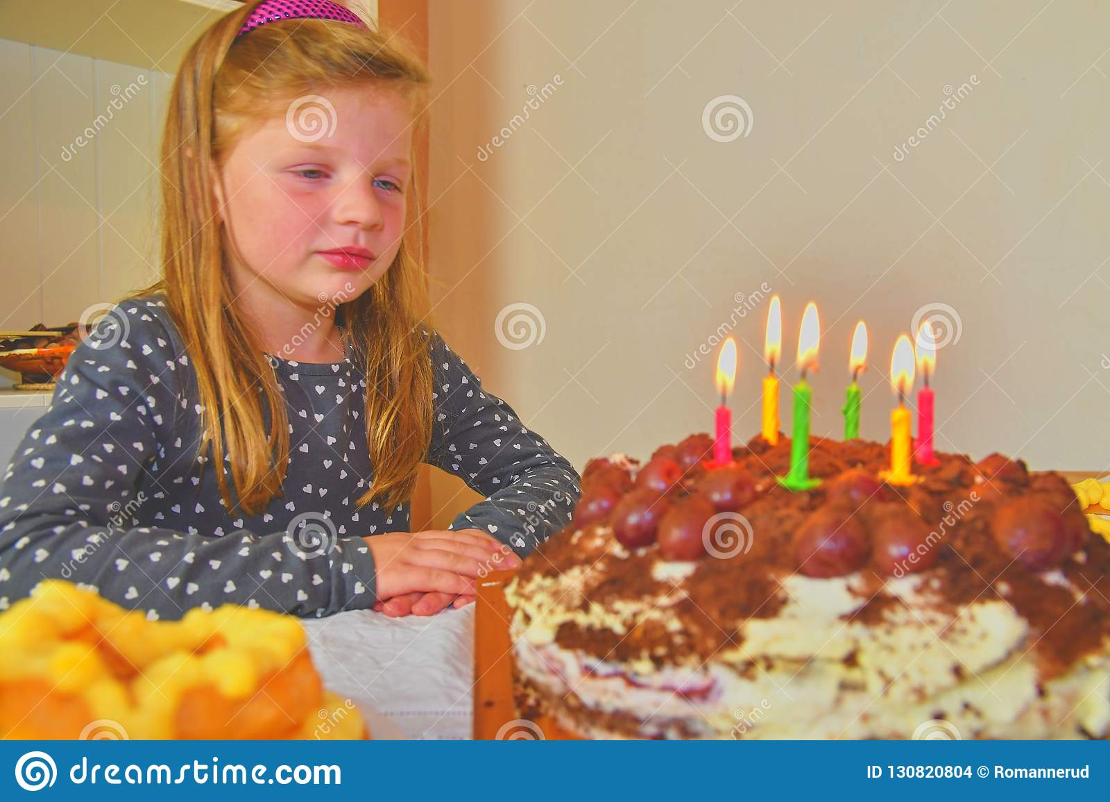 Little girl looking on her birthday cake. Small girl celebrating her six birthday. Birthday cake and little girl