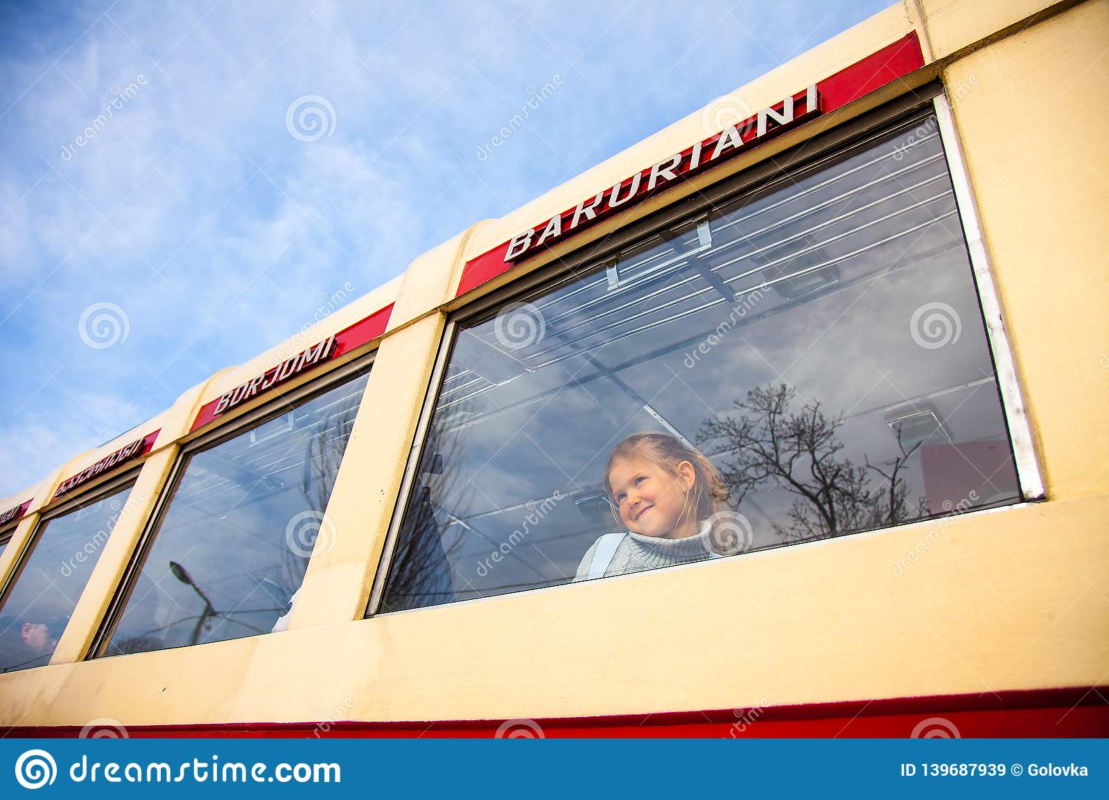 Little girl looking at window of old Georgian train Kukushka, view from outside