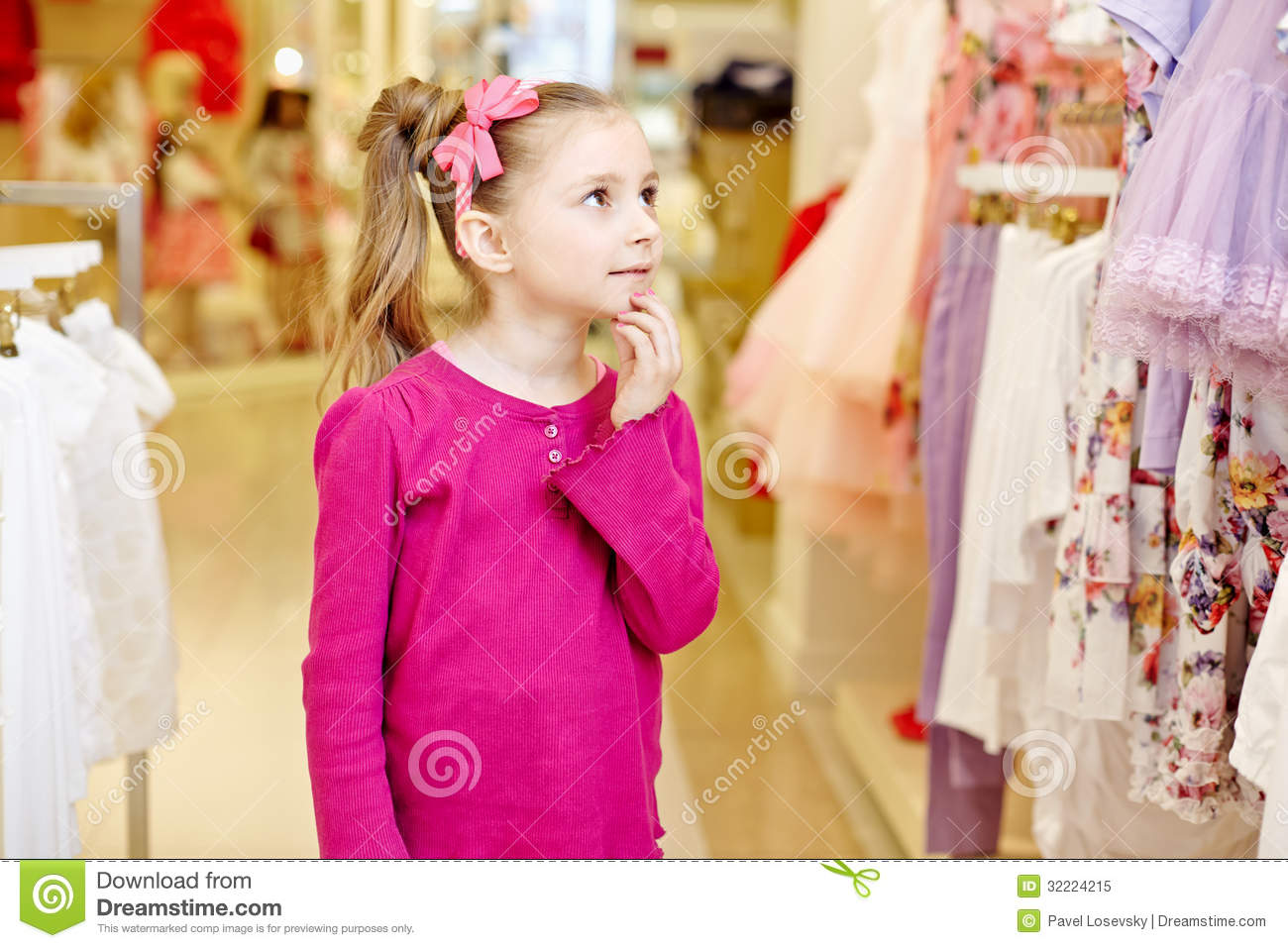 little girl looks upon dresses hanging at stand royalty