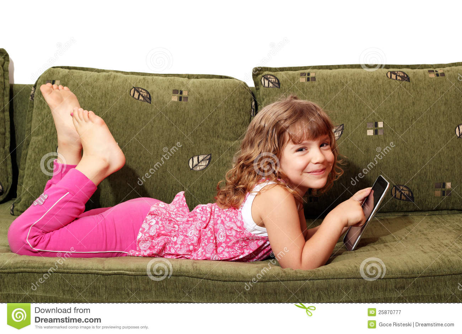 little girl lying Little girl lying on bed with tablet