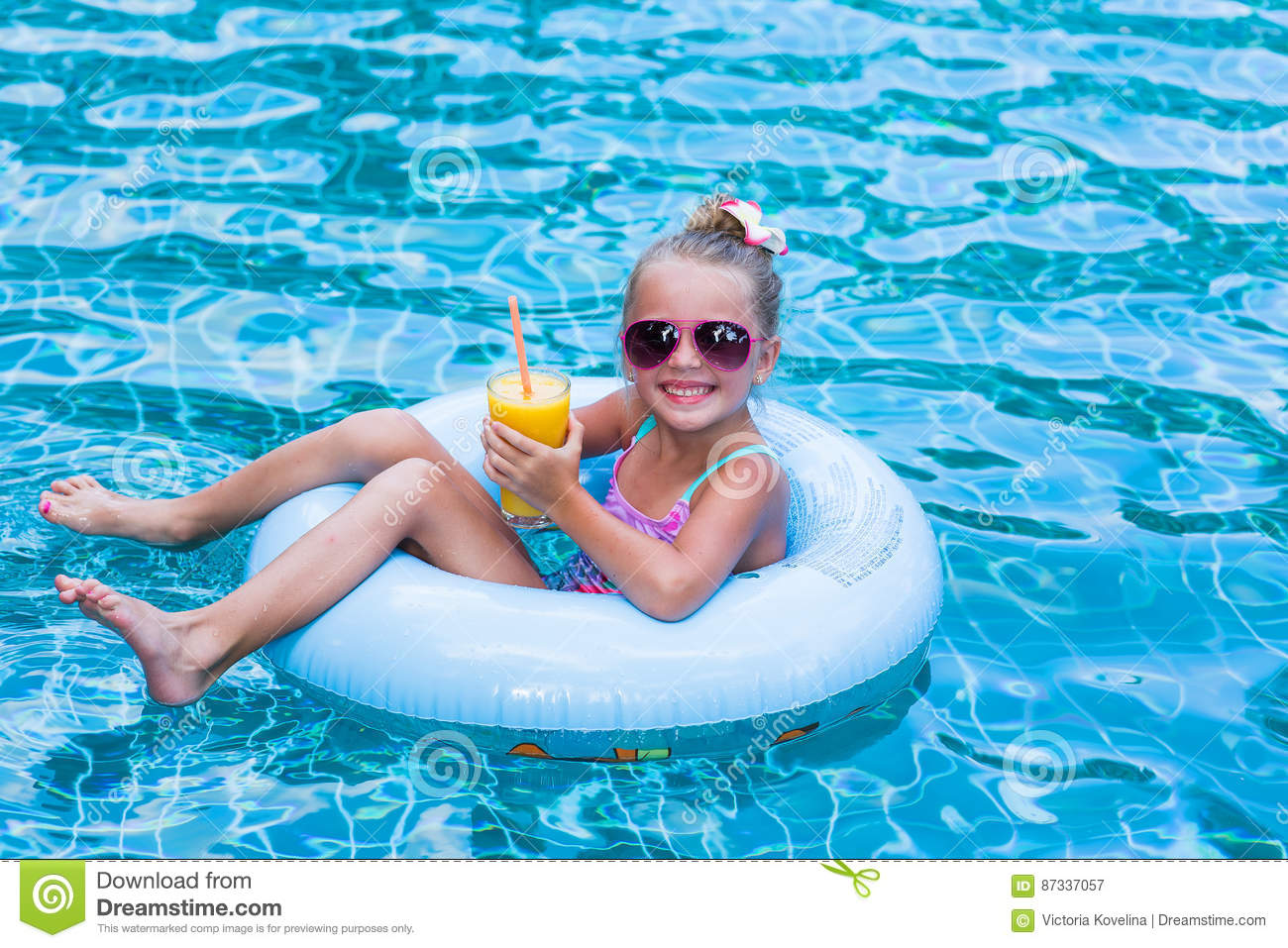 Little Girl Lying On Inflatable Ring In Swimming Pool In