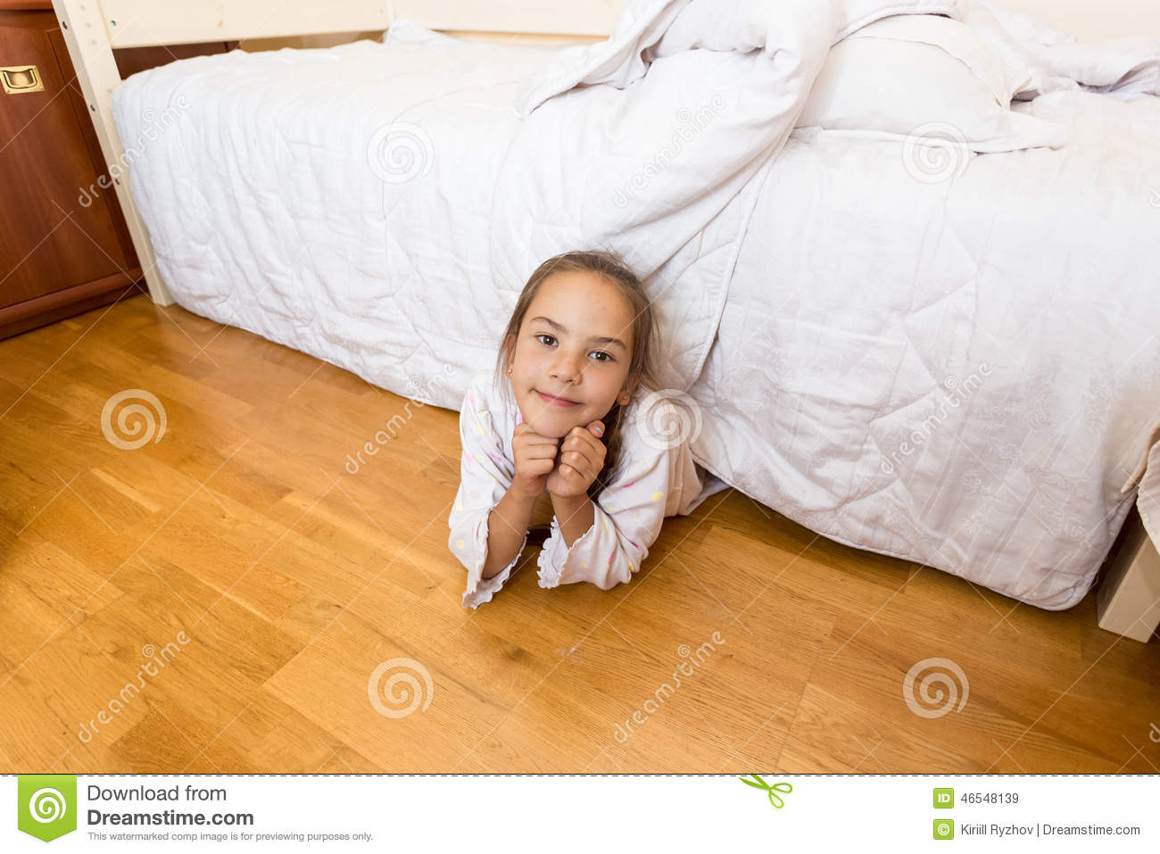 Little Girl Lying Under Bed At Home And Looking At Camera