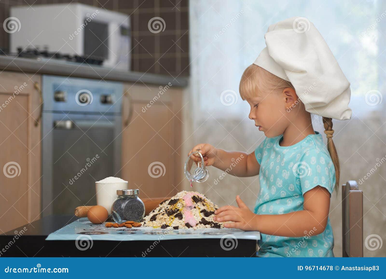 Little girl making dough in a shape of volcanoe
