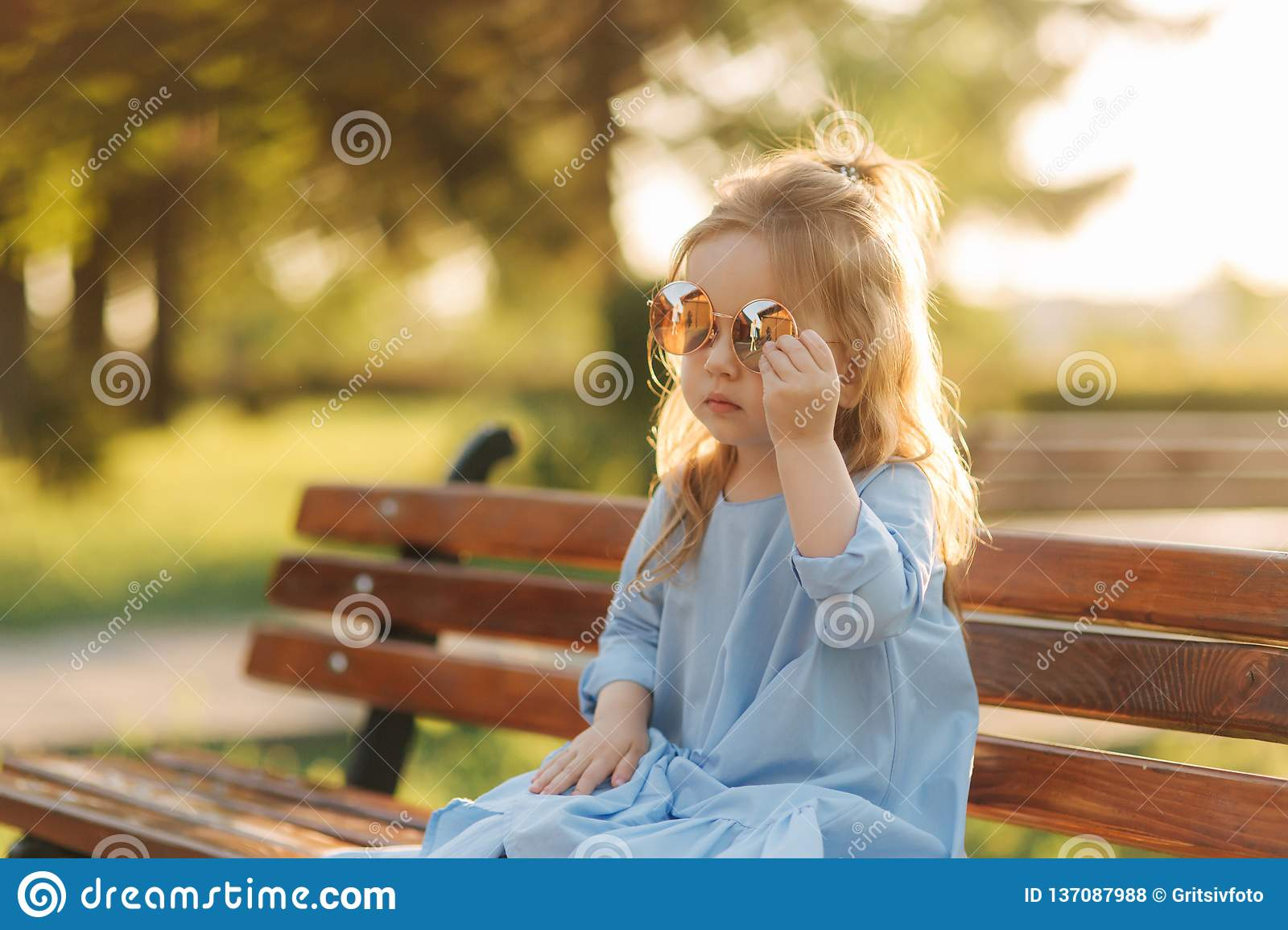 Little girl model in blue dress and sun glasses sits on a bench in the park