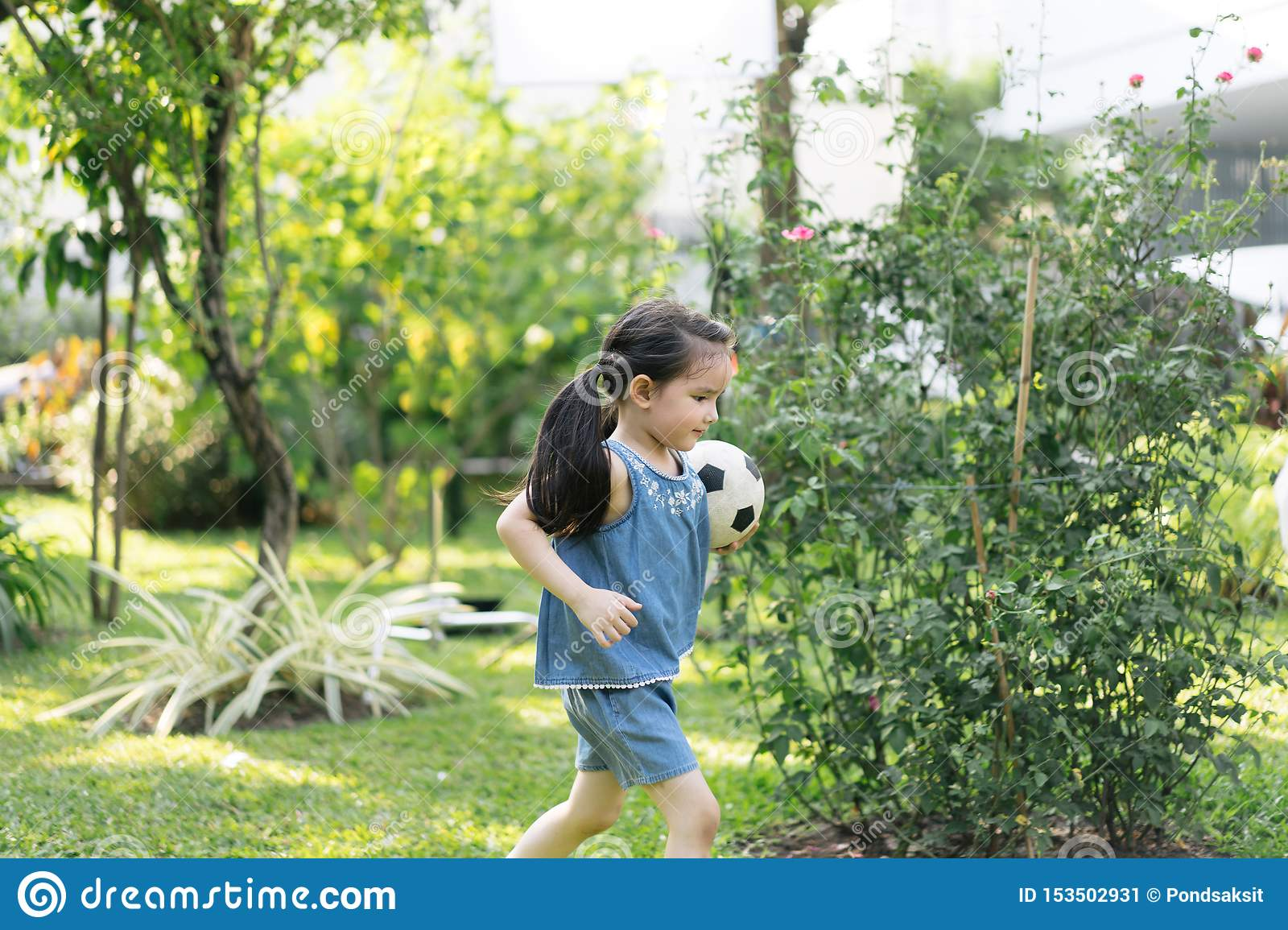 Little girl in nature park . cute kid holding playing football.
