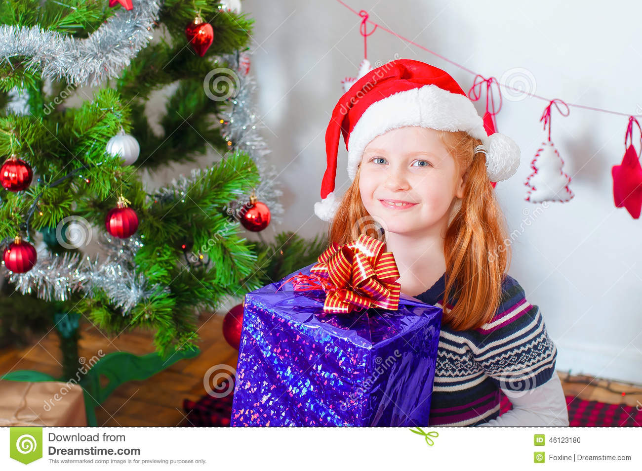 Little Girl Near The Christmas Tree With Gifts Stock Photo