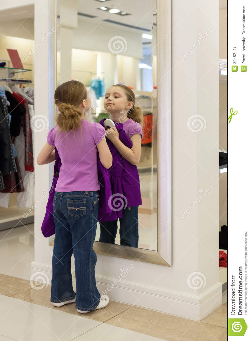 Little girl near a mirror try on clothes in a store stock for Mirror warehouse near me