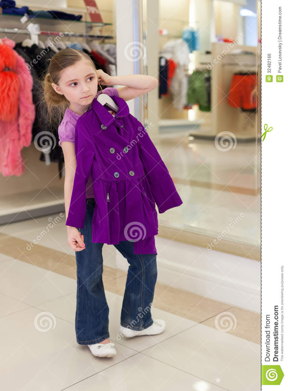 Little girl near a mirror try on clothes in a modern store childrens