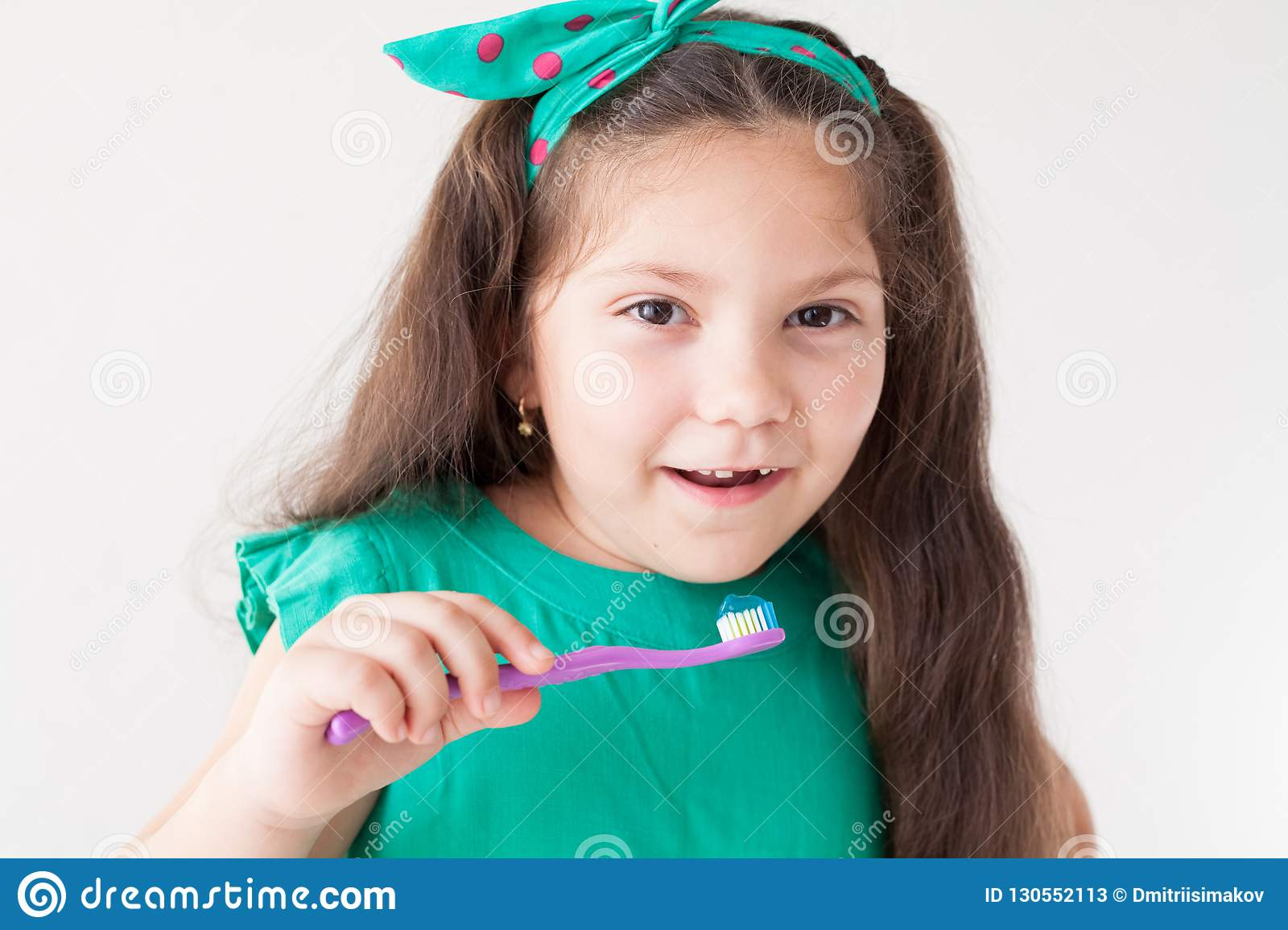 Little girl with no teeth with a toothbrush in dentistry