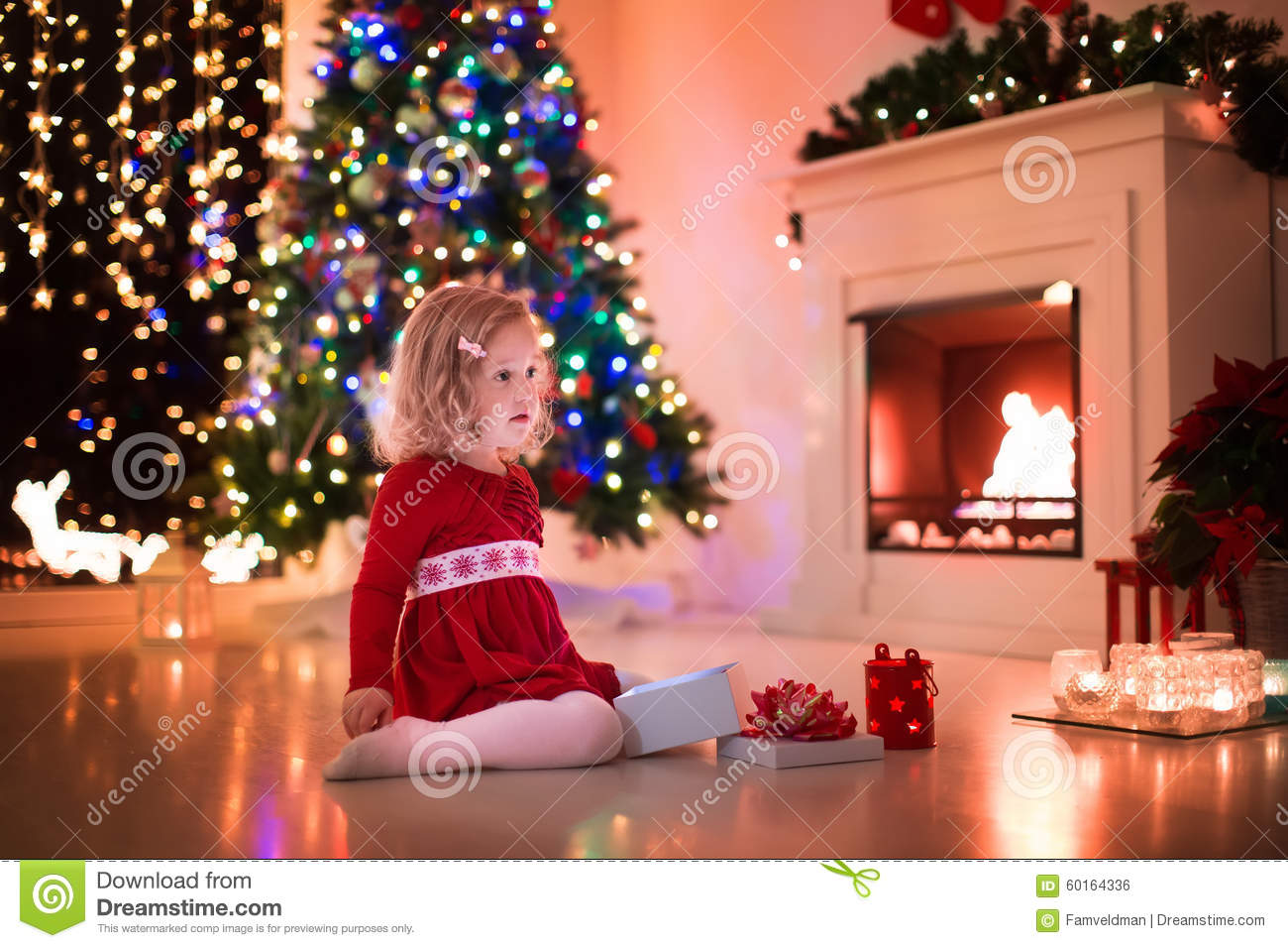 Little Girl Opening Christmas Presents At Fire Place Stock