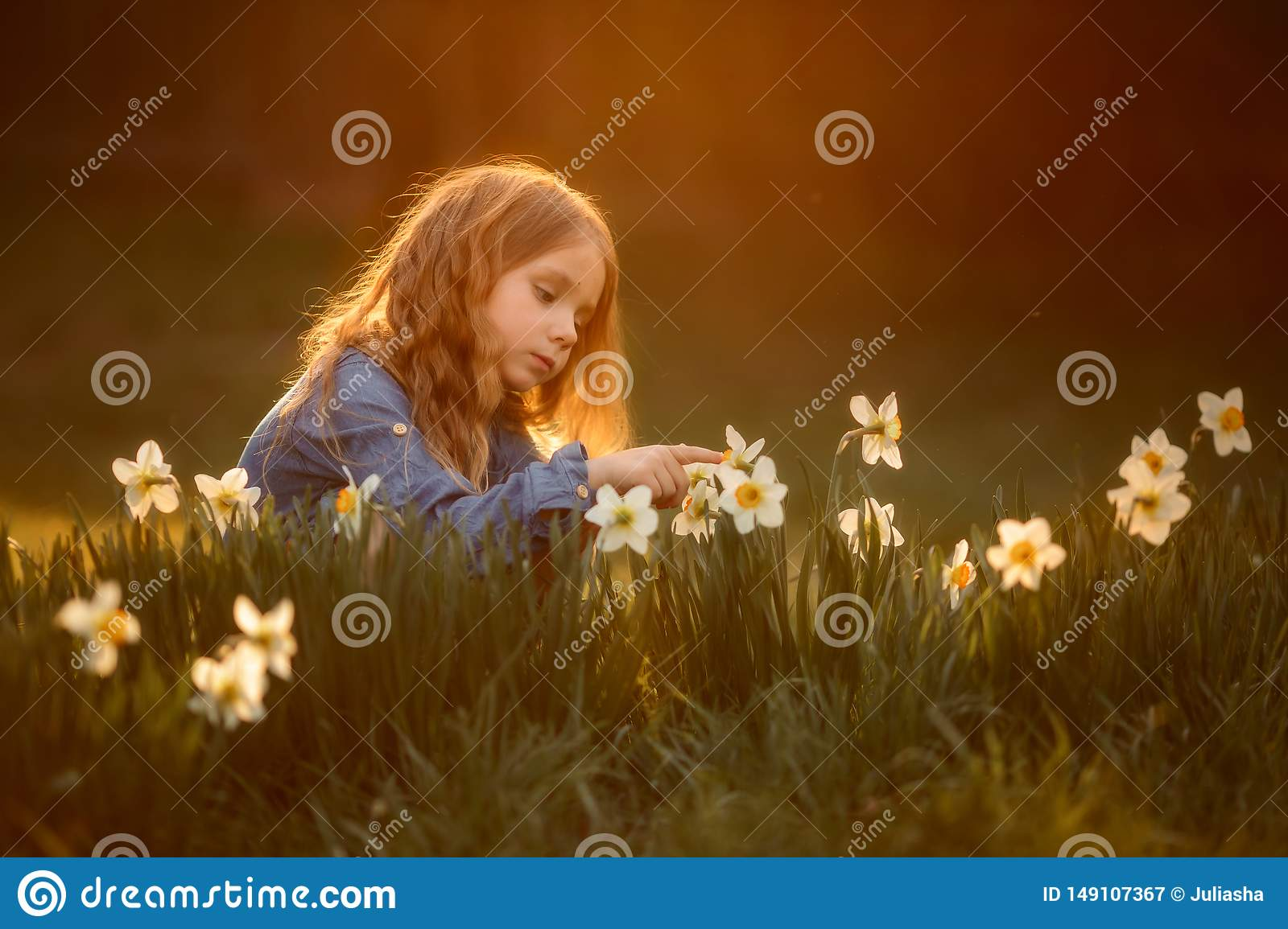 Little girl outdoor portrait near narcissus flowers at sunset