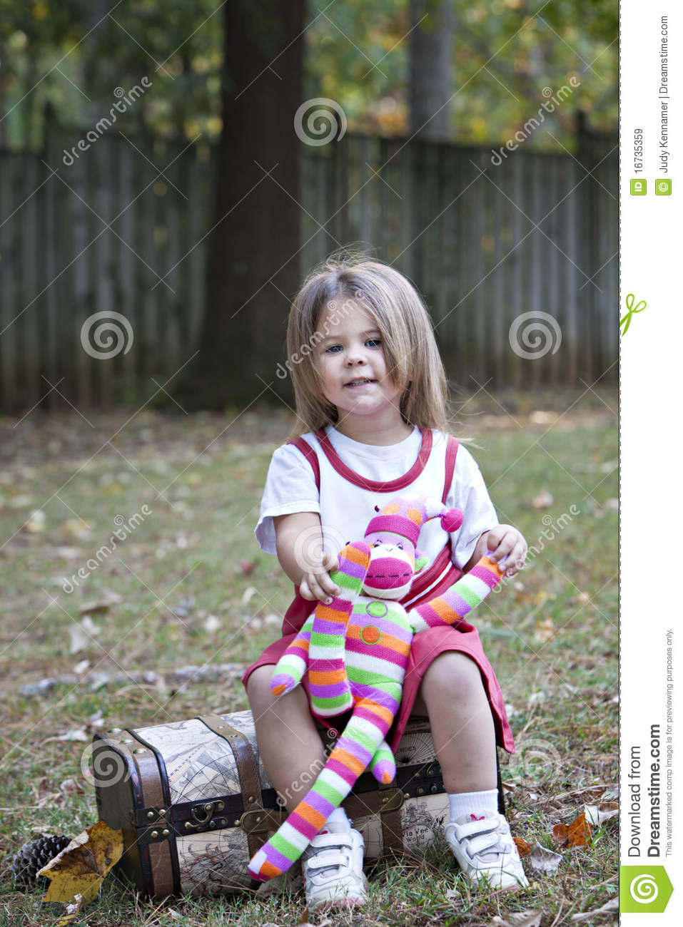 little girl outdoors with toy monkey royalty free stock