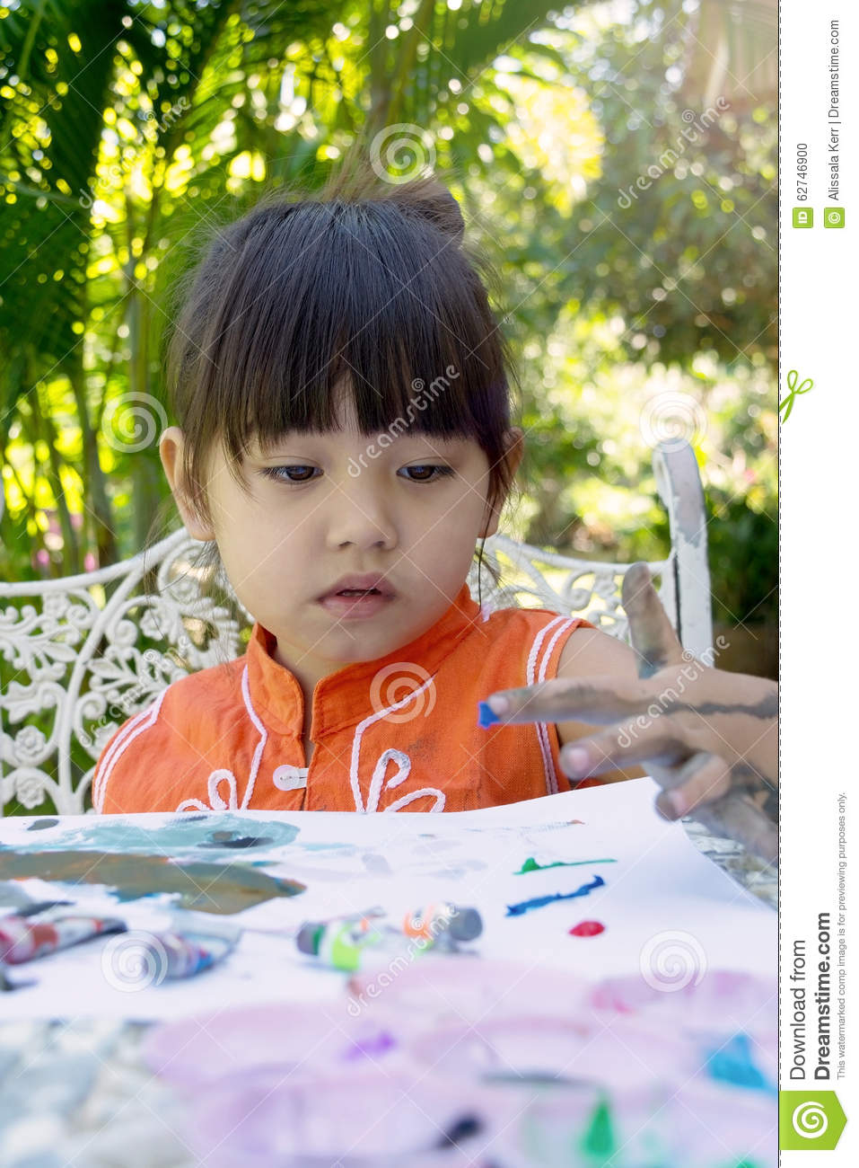 Little girl painting in garden at home